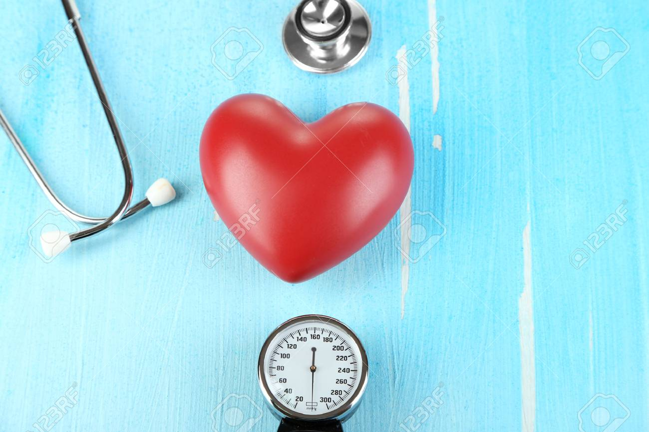 Tonometer, stethoscope and heart on wooden table close-up Stock Photo - 22587282