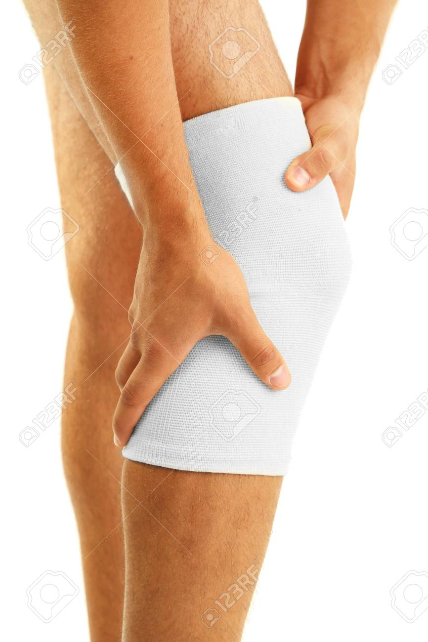 Young Man With Elastic Bandage On Knee Isolated On White Stock