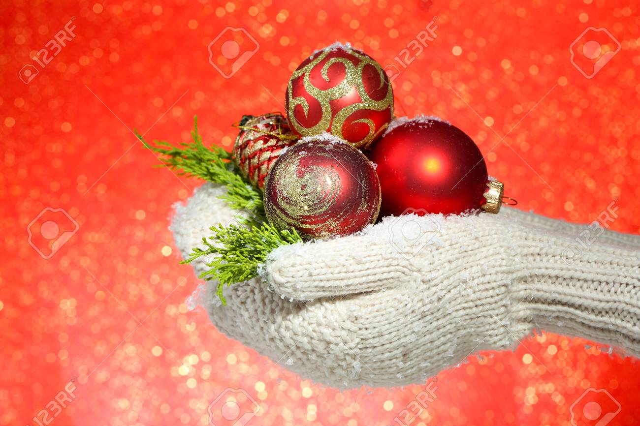 Female hands in mittens christmas tree balls on color stock