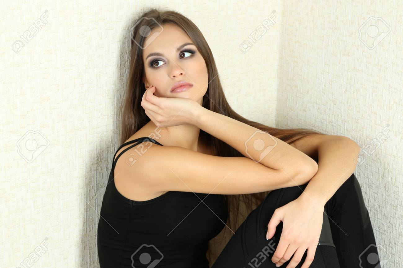 Lonely sad woman sitting on floor near wall Stock Photo - 24340584