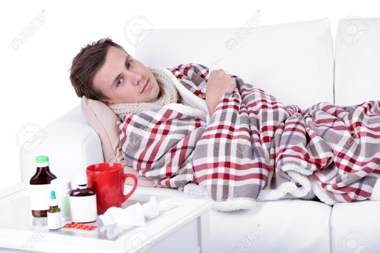 Guy wrapped in plaid lies on sofa is ill Stock Photo - 26375712