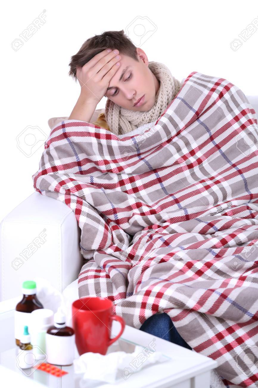 Guy wrapped in plaid sitting on sofa is ill Stock Photo - 26375714