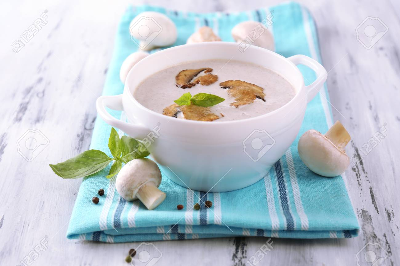 Mushroom soup in white pot, on napkin,  on wooden background Stock Photo - 26424993