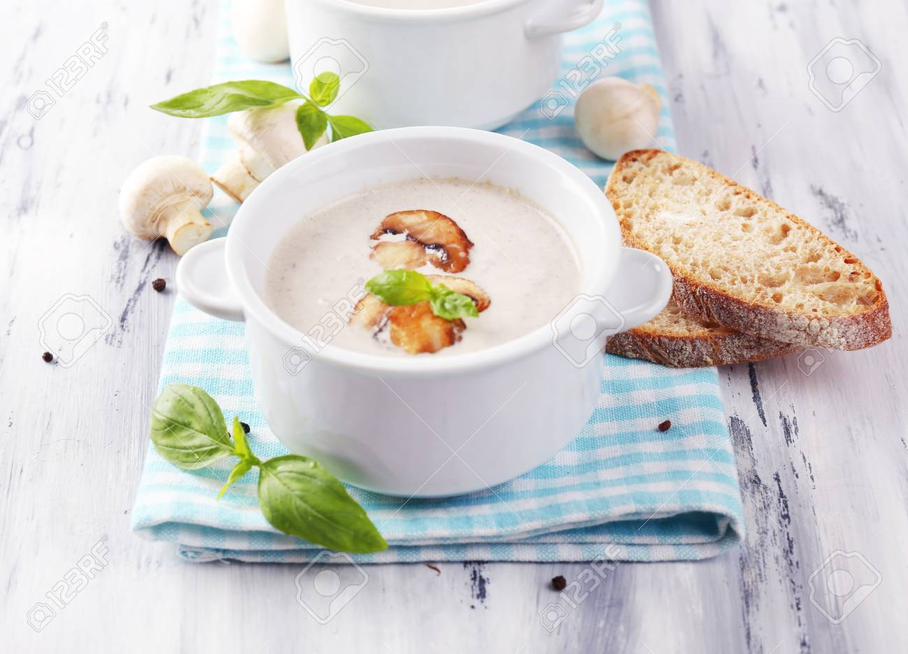 Mushroom soup in white pots, on napkin,  on wooden background Stock Photo - 28545894