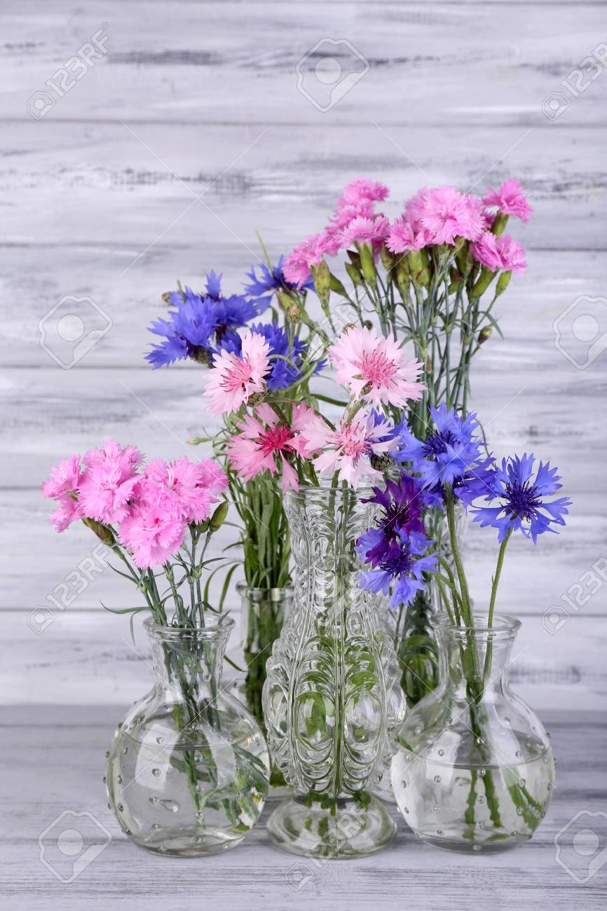 123RF.com & Beautiful summer flowers in vases on grey wooden background