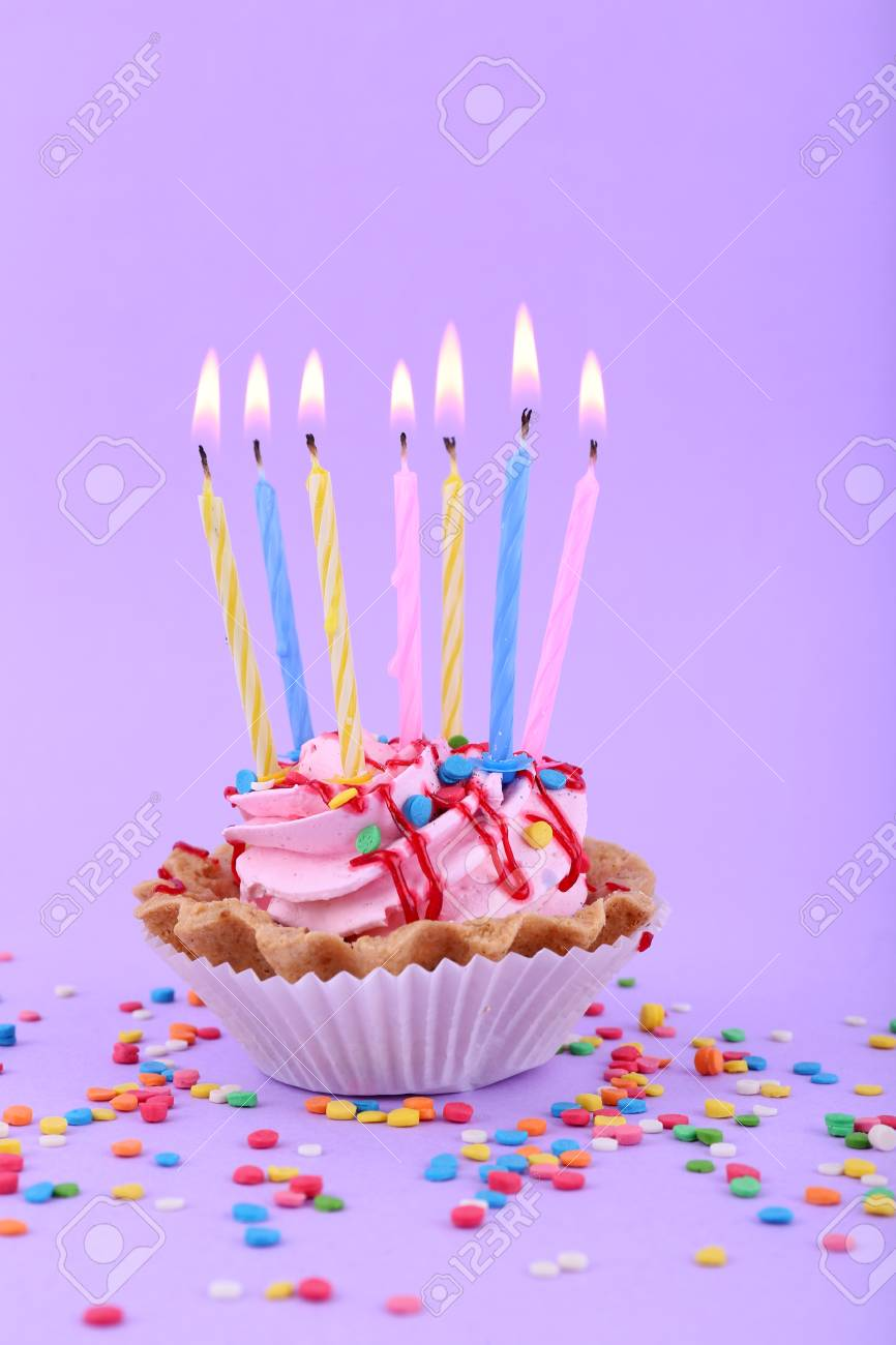 Birthday Cup Cake With Candles And Colorful Sparkles On Purple Background Stock Photo