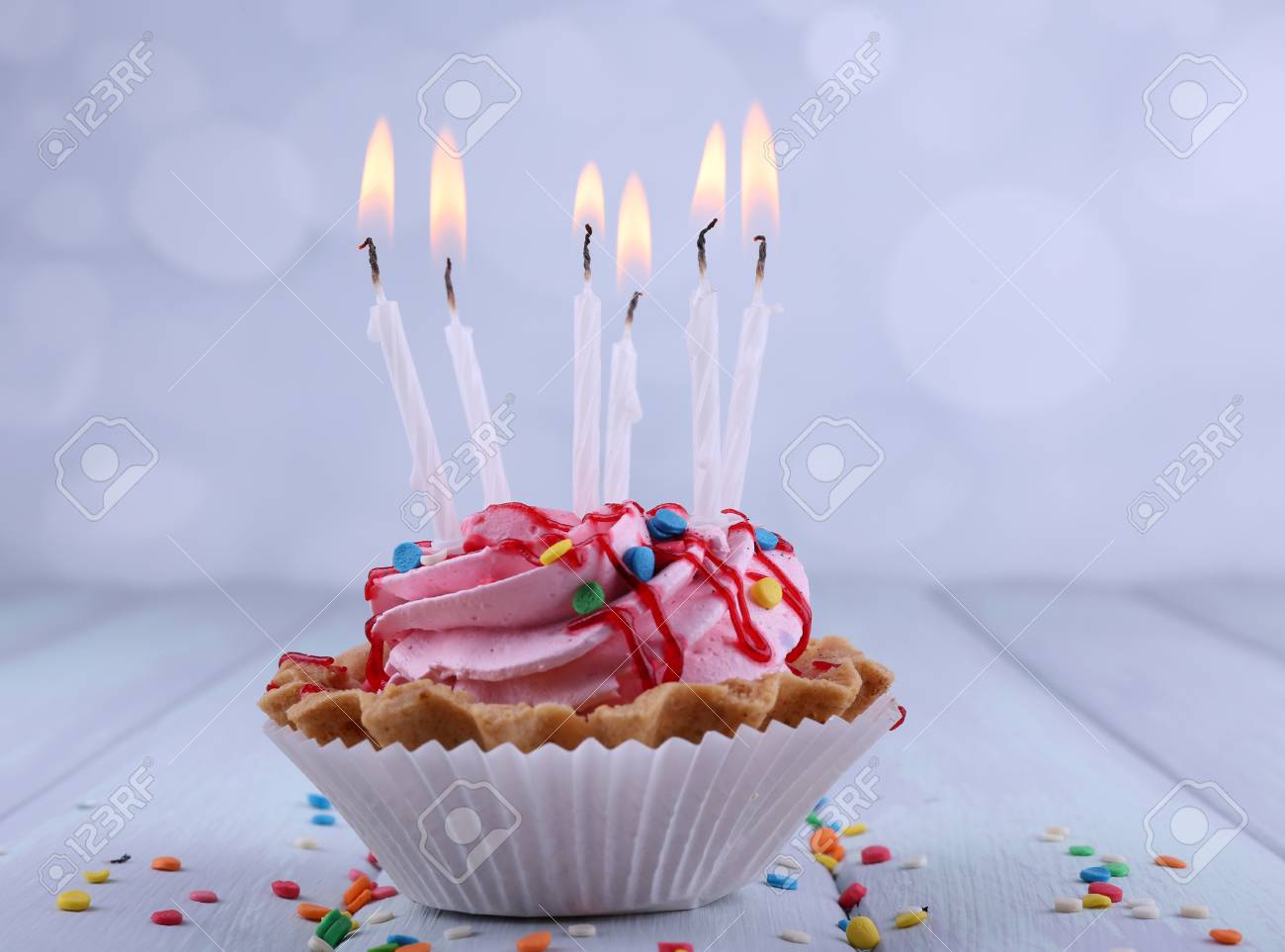 Birthday Cup Cake With Candles And Sparkles On Color Wooden Table