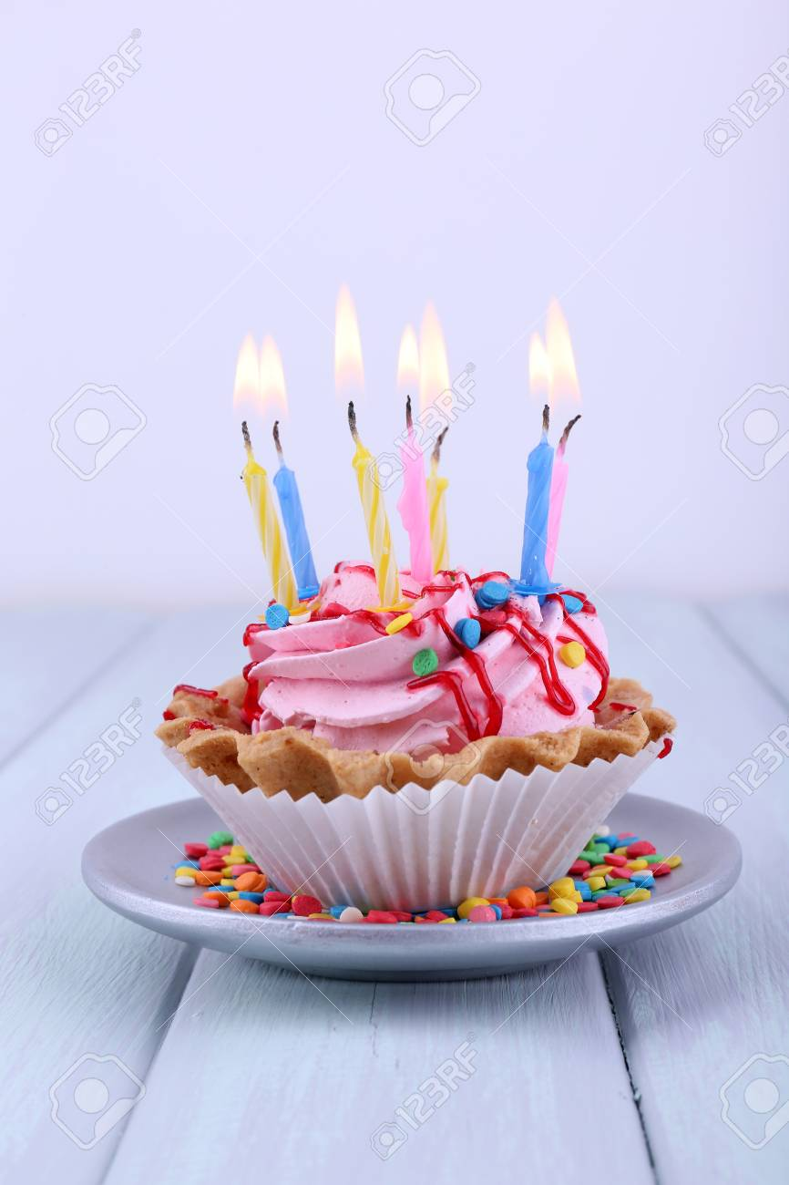 Birthday Cup Cake With Candles On Saucer And Sparkles Color Wooden Table Light Background