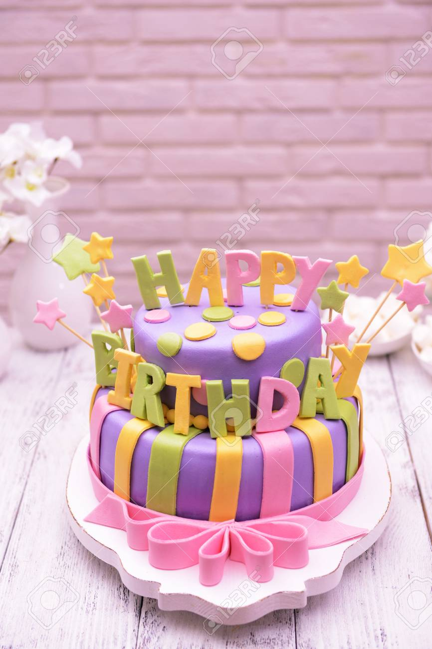 Delicious Birthday Cake On Table On Brick Wall Background Fotos
