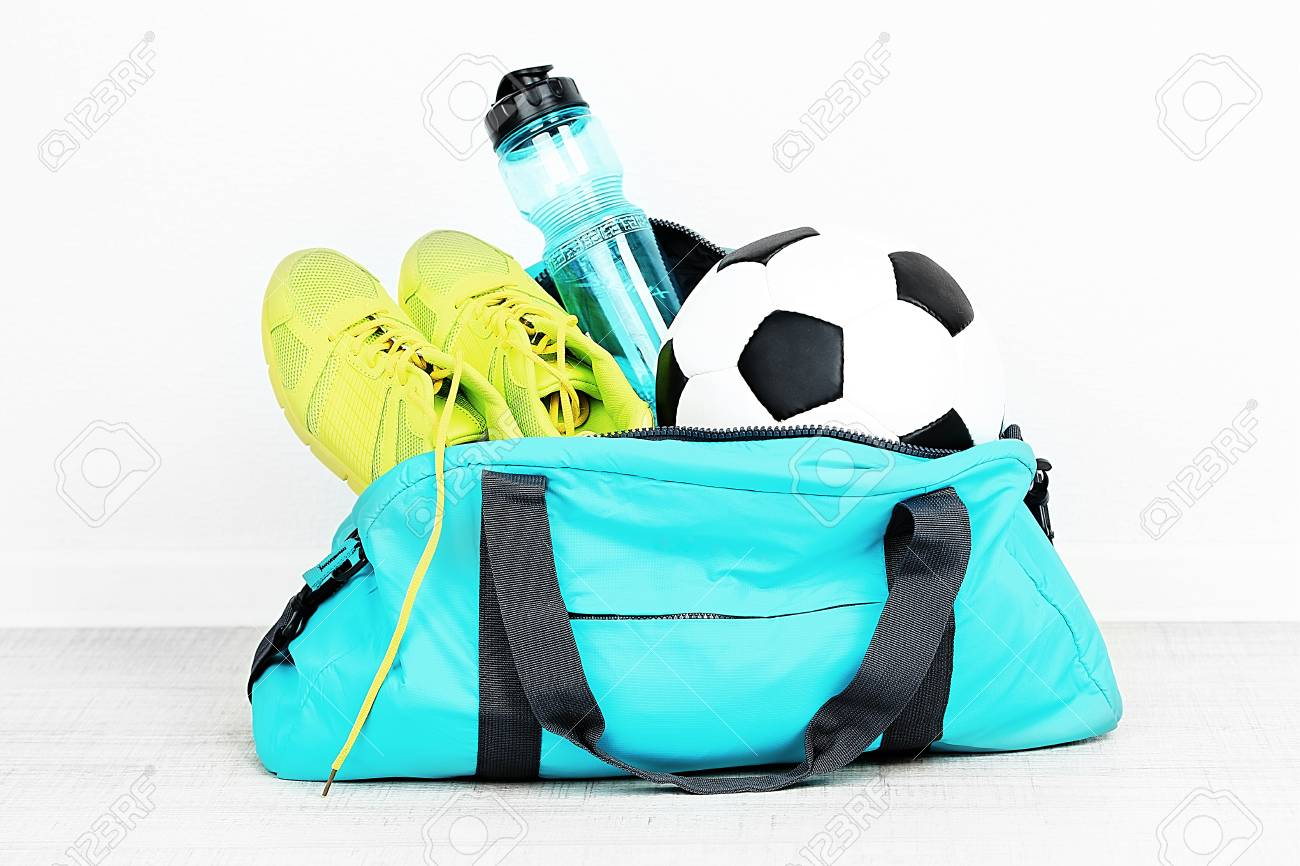 Sports bag with sports equipment in room - 100038980