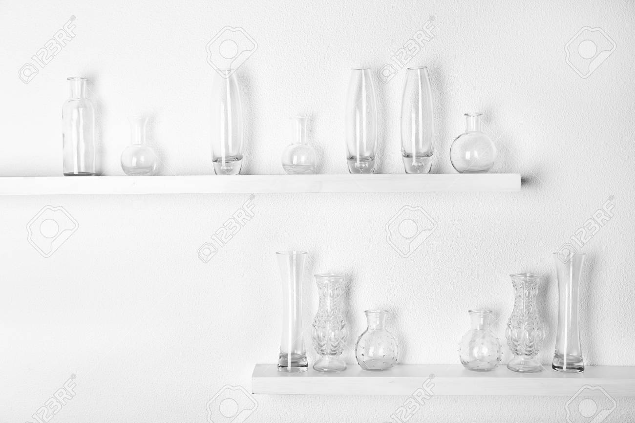 Decorative glass vases on wooden shelf on white wallpaper background stock photo 101762270