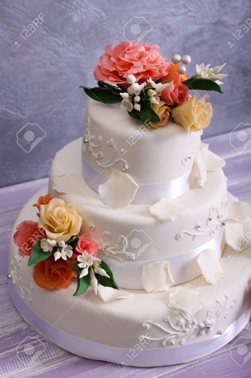 White Wedding Cake Decorated With Flowers On Grey Background Stock
