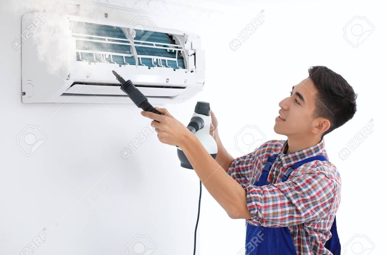 Technician cleaning air conditioner indoors - 110545738