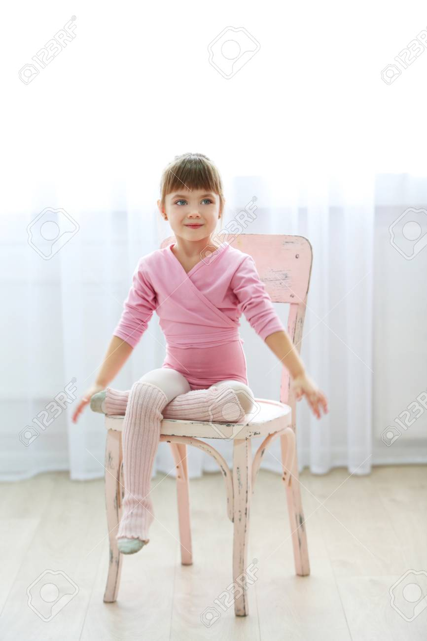 8980b4a7680d Little Cute Girl In Pink Leotard Sitting On Chair At Dance Studio ...