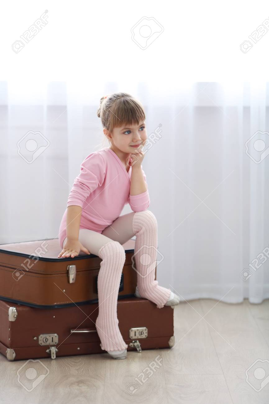 31dcfd43fbaa Little Cute Girl In Pink Leotard Sitting On Suitcases At Dance ...