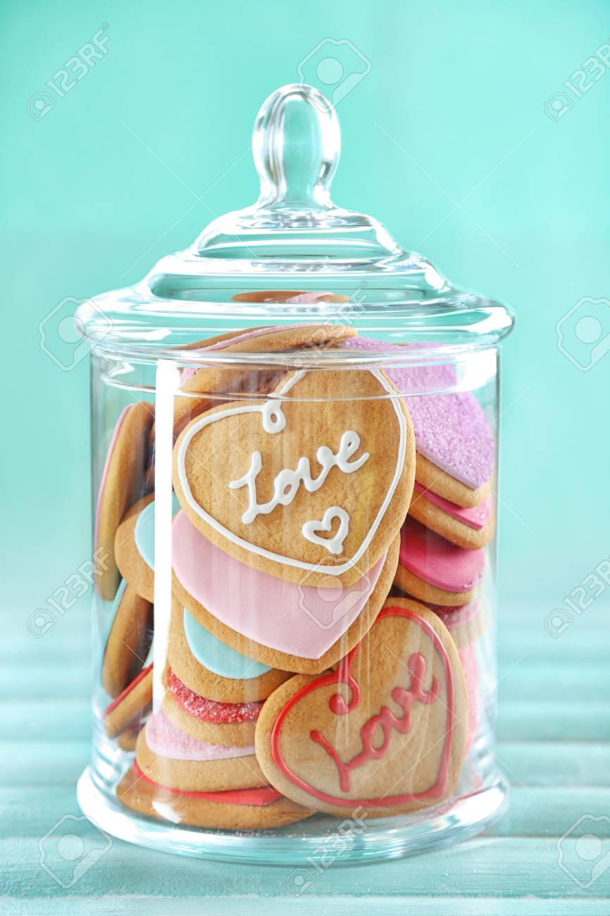 Assortment of love cookies in jar on blue background - 105831660