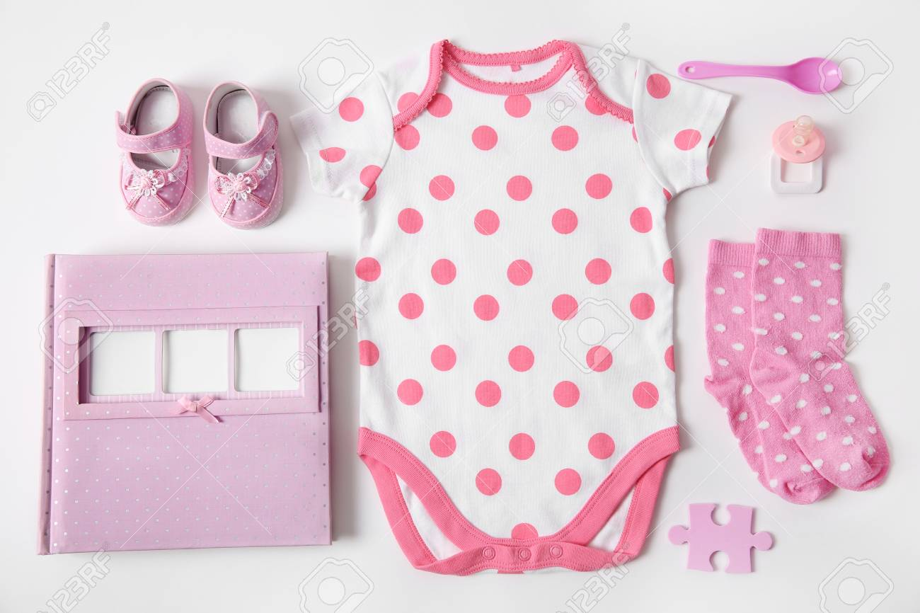 Baby Clothes With Photo Album Spoon And Nipple On White Background