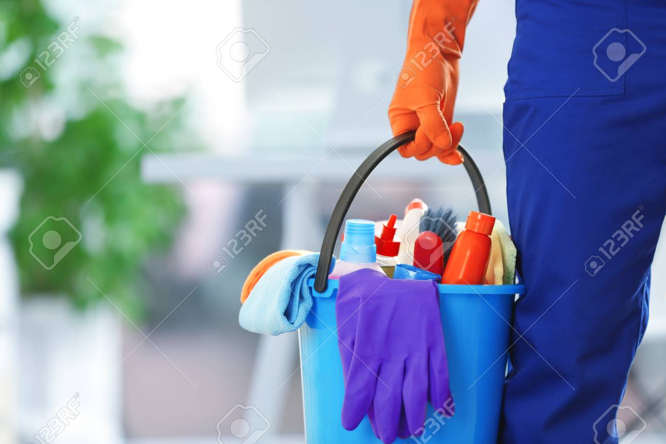 holding cleaning products and tools on bucket, close up - 106018599