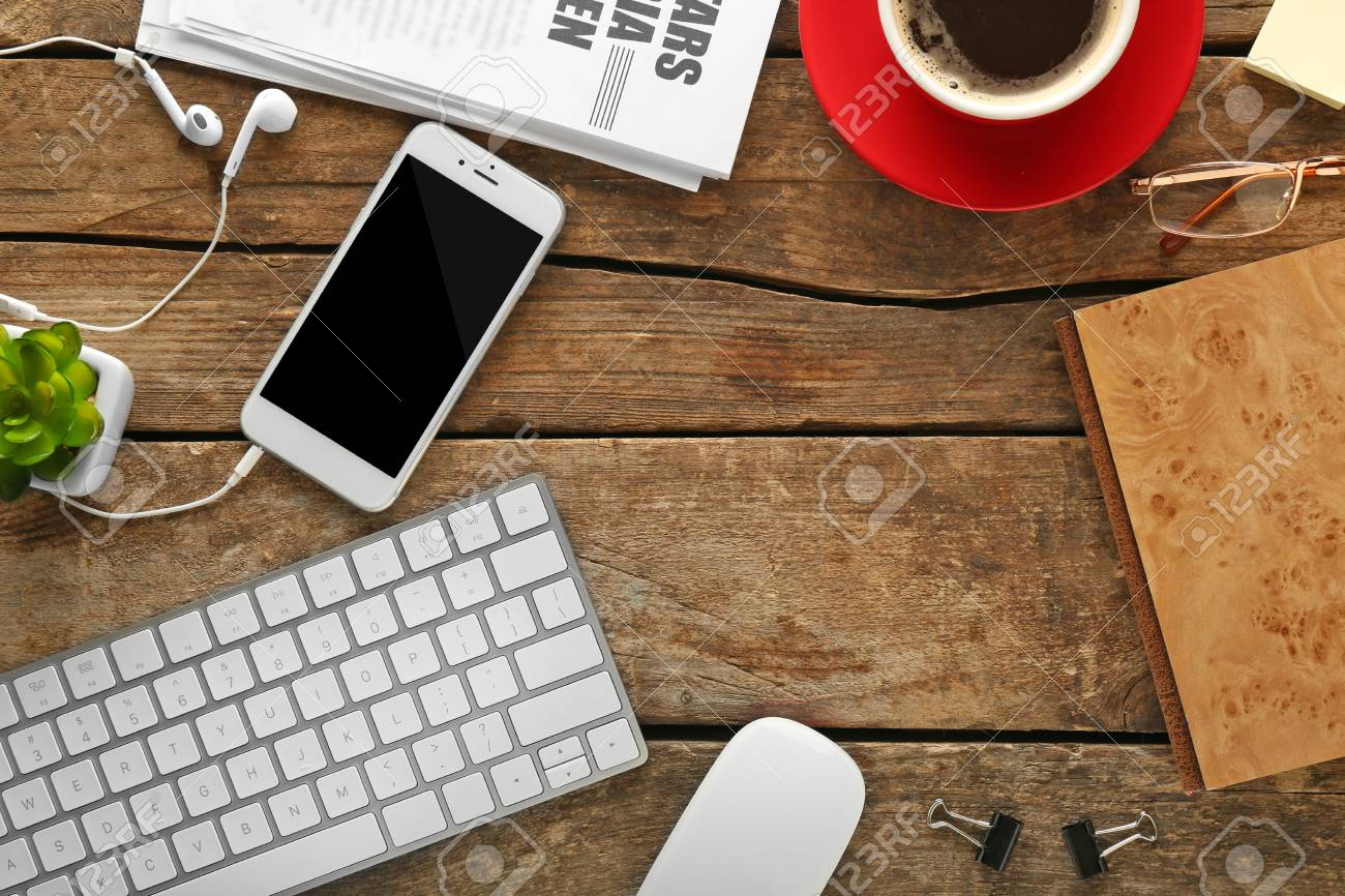 Workplace with mobile phone, peripheral devices and newspaper on wooden table - 106314556