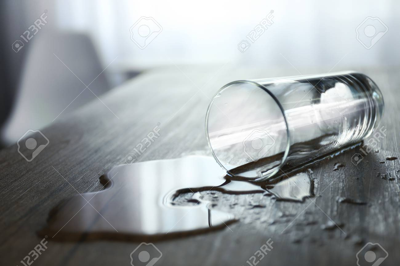 Glass of water spilled on wooden table - 106457653