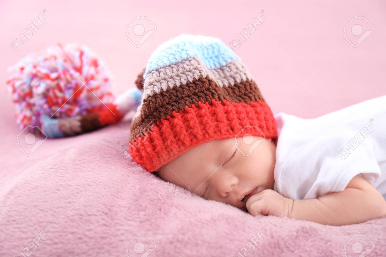 9e114598b Cute Little Baby With Wicker Cap Sleeping On Bed At Home Stock Photo ...