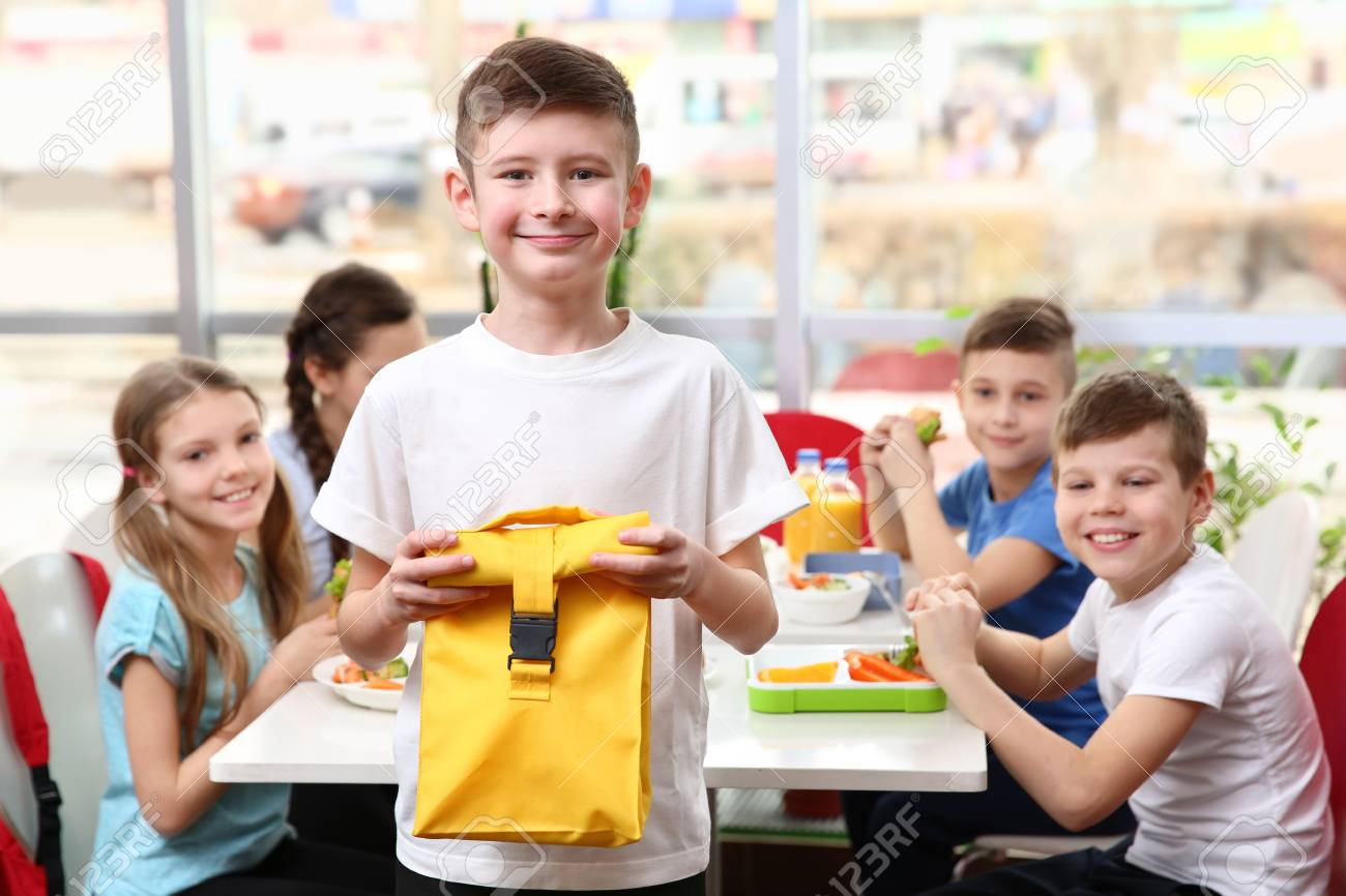 Fabulous Cute Boy Holding Lunch Bag And Children Eating At Table In School Download Free Architecture Designs Embacsunscenecom