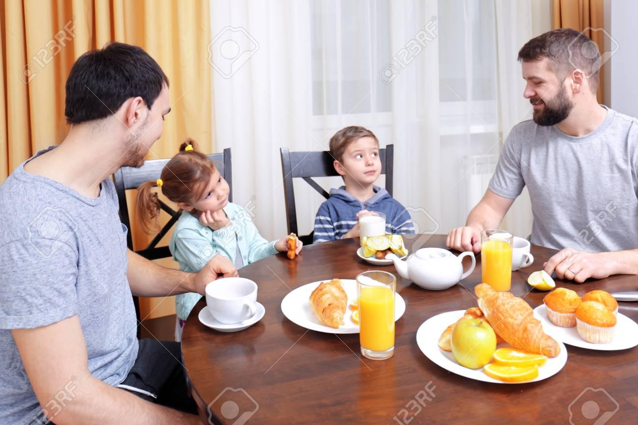 Male couple with children having breakfast in kitchen - 110839864