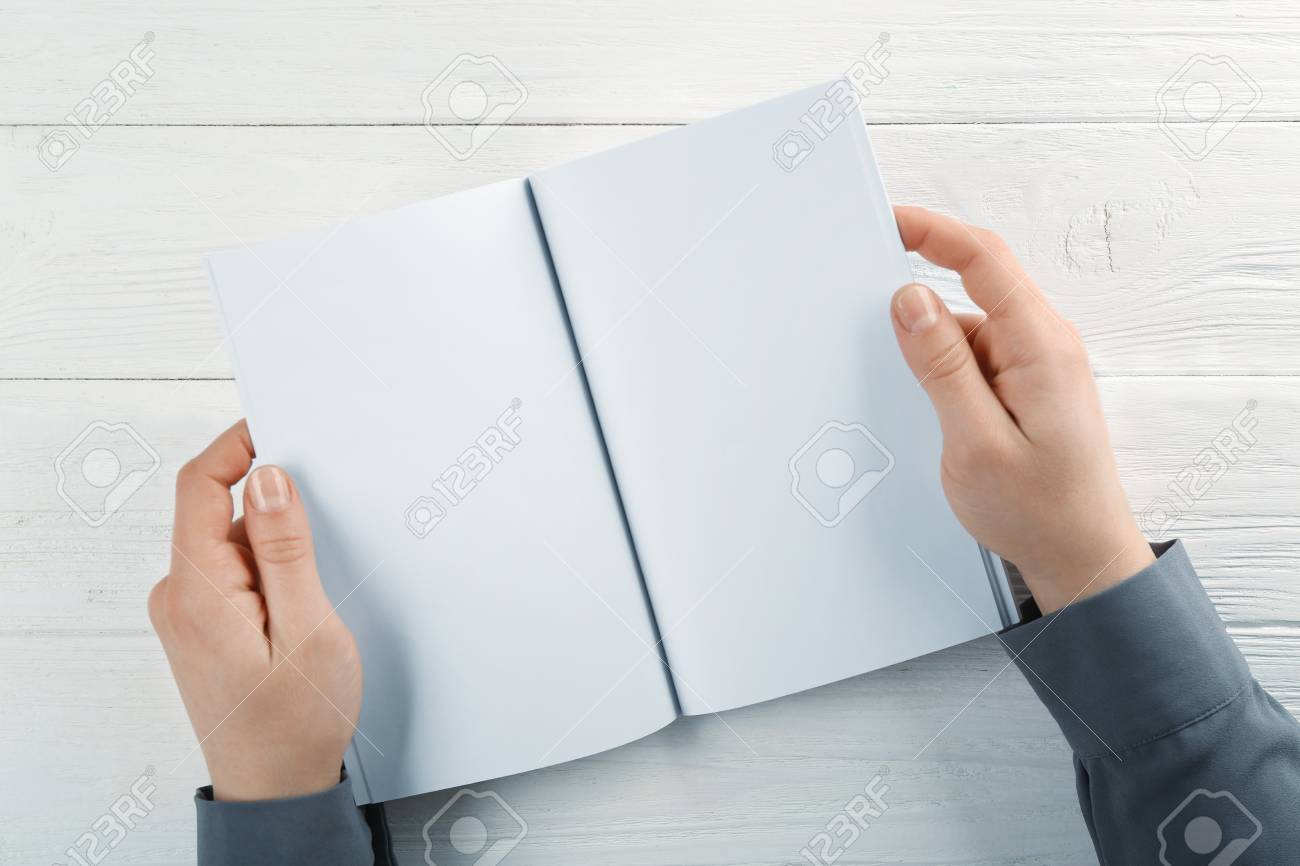 female hands holding blank brochure on wooden background stock photo