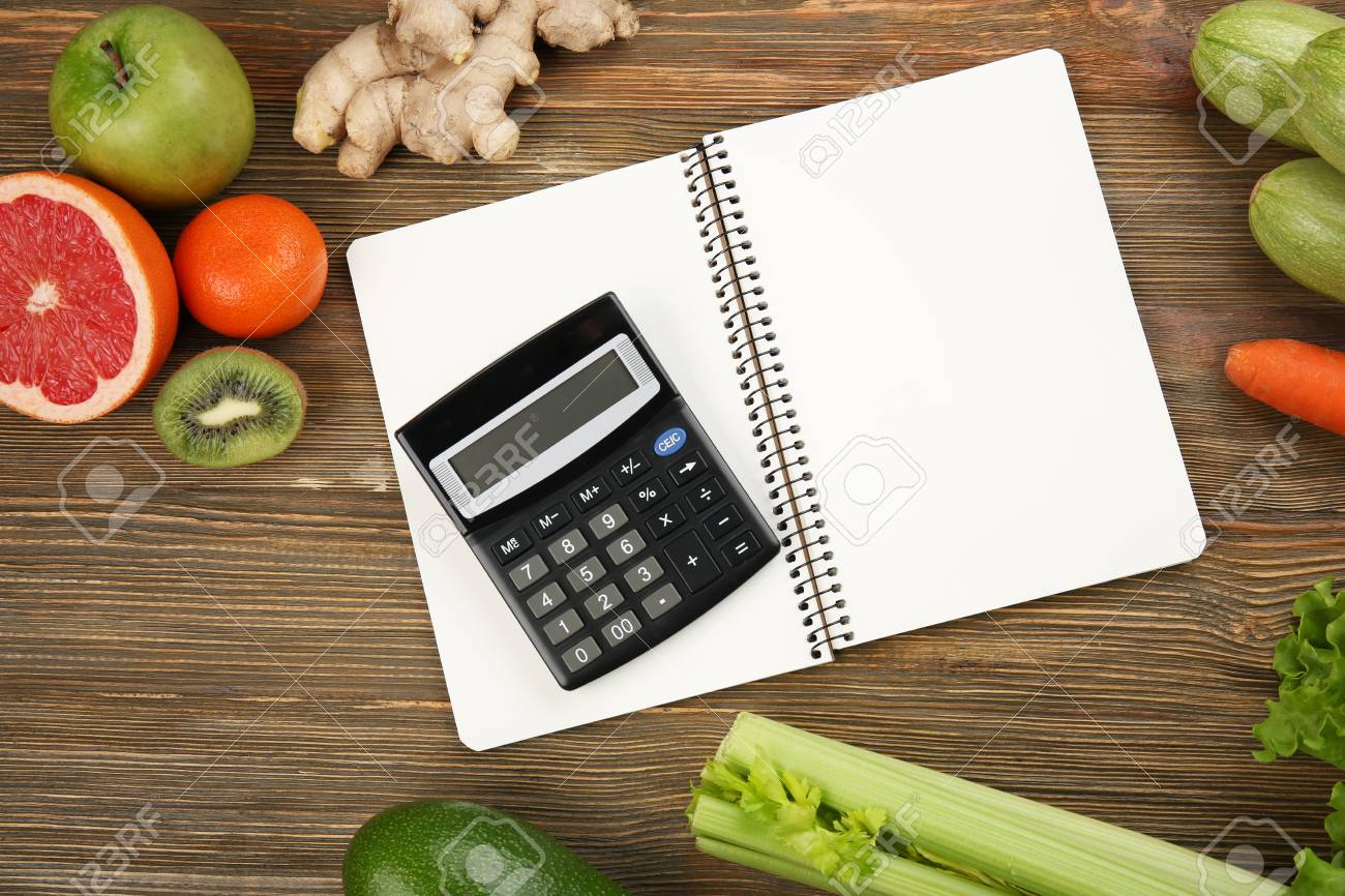 diet concept calculator notebook and different groceries on
