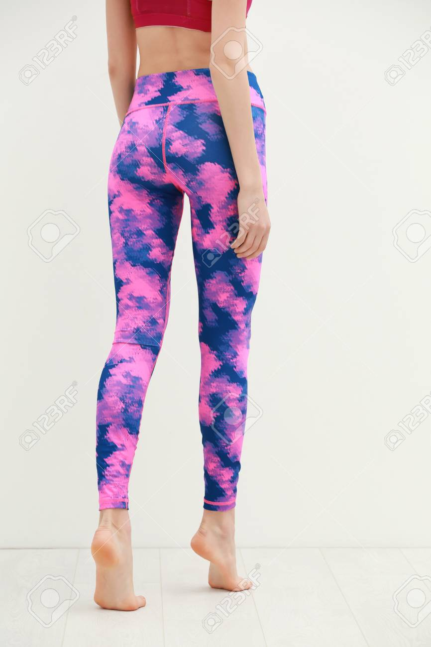 cecf01d0c4117 Stock Photo - Young woman in beautiful yoga pants on light wall background