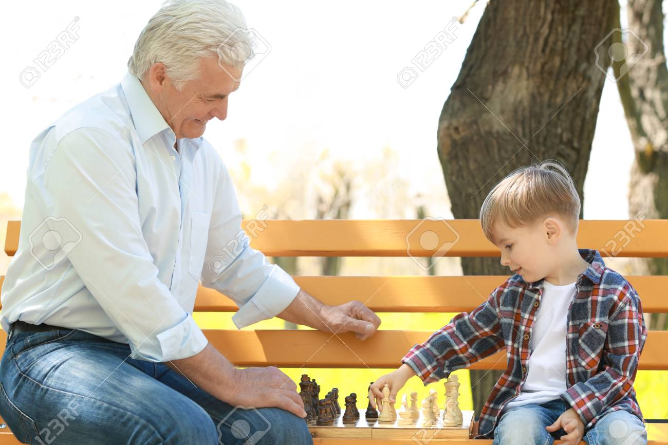 Cute little boy with his grandfather playing chess on bench in spring park - 110645379