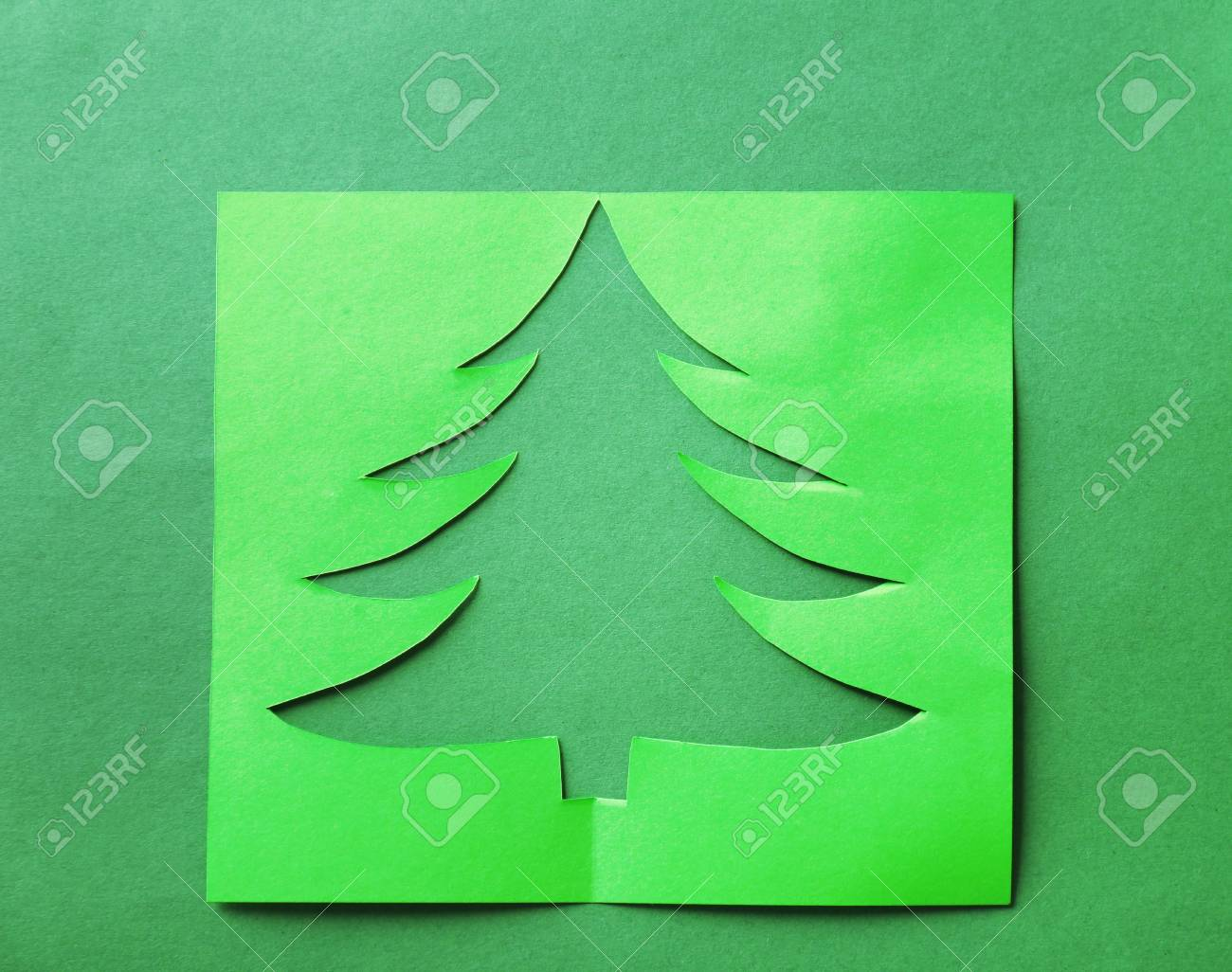 Sheet Of Paper With Cut Out Christmas Tree On Color Background Stock Photo