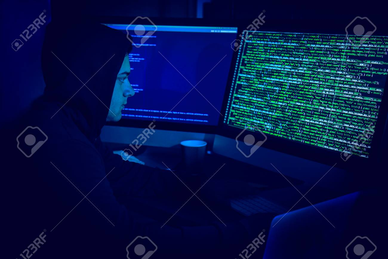 Hacker using computer in dark room