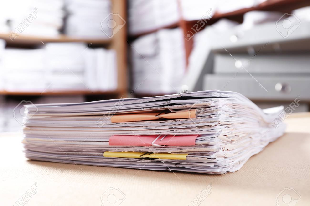 Stack of old paper documents on table in archive - 112544940