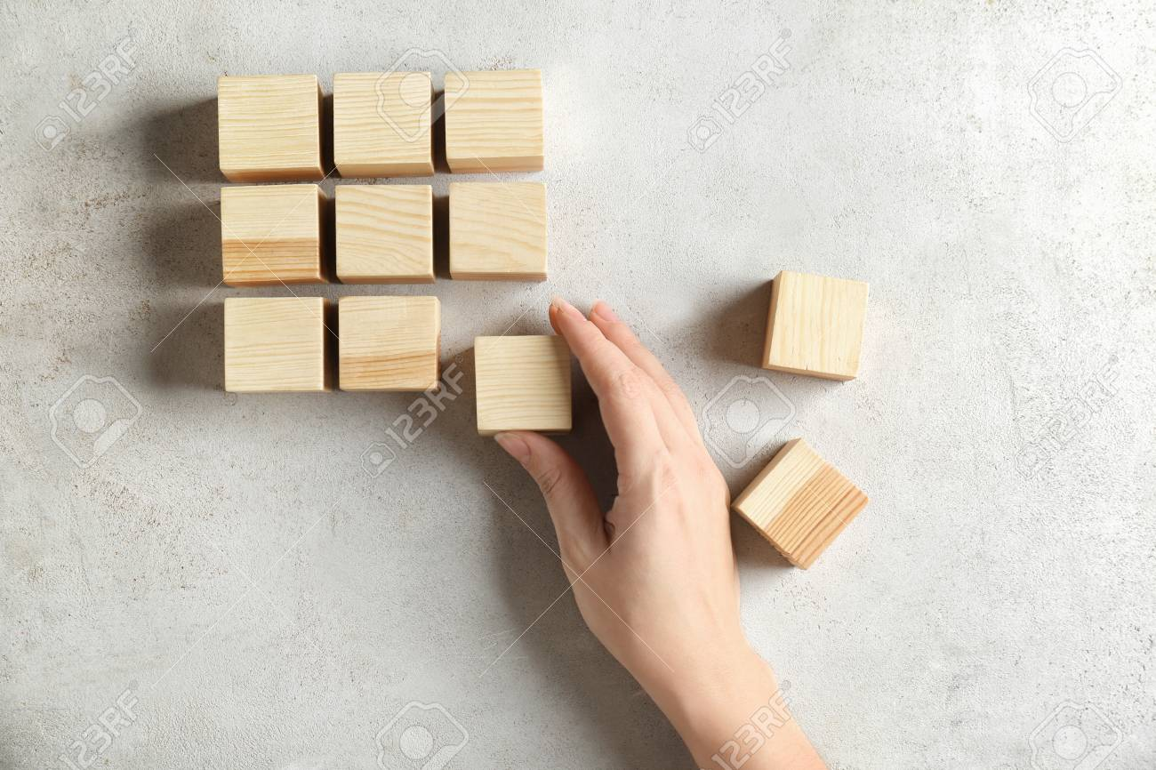 Woman With Wooden Cubes On Light Background Unity Concept