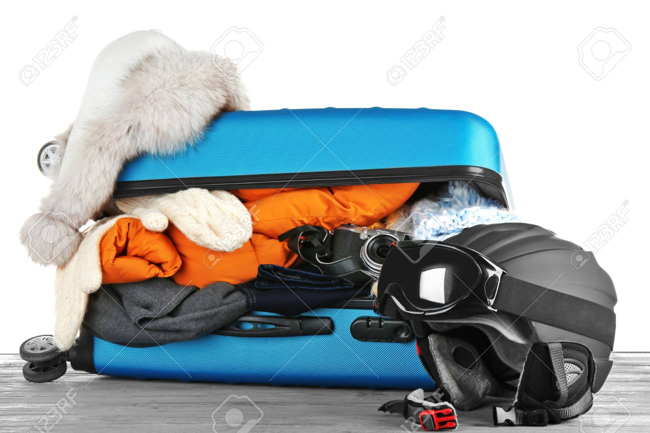 a4d7425cbe1 Open suitcase with warm clothes and ski outfit on wooden table against  white background. Winter