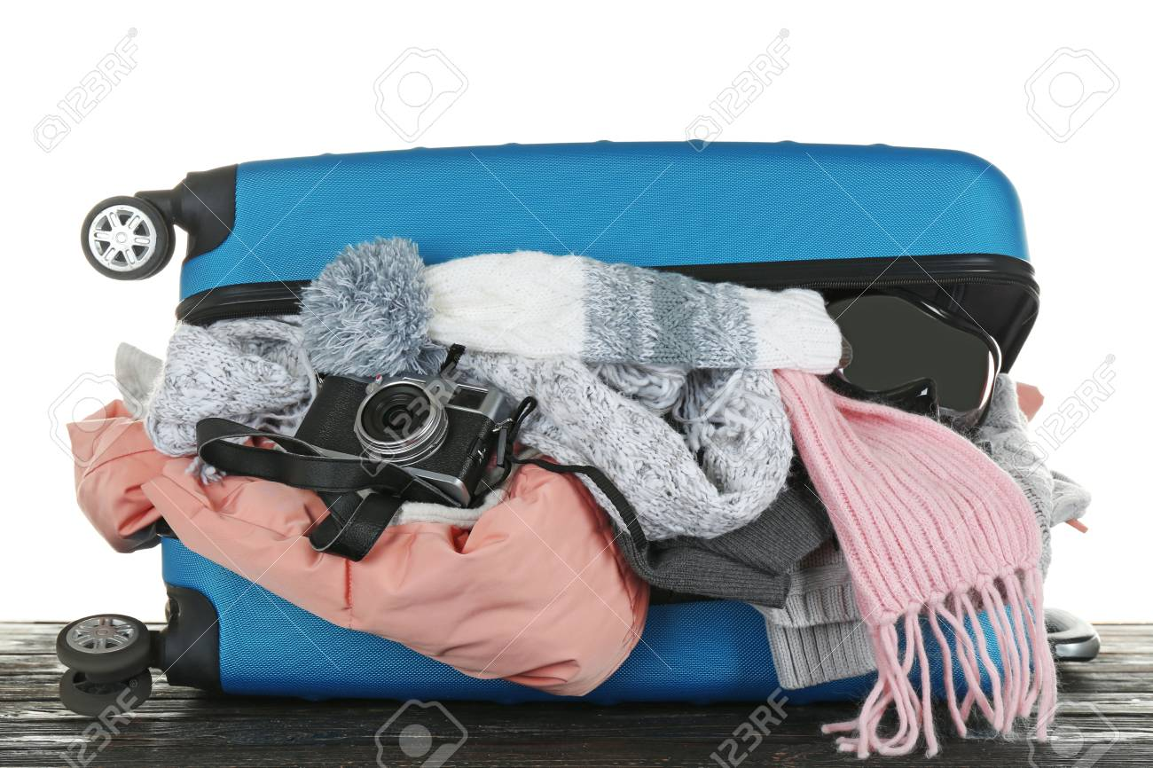 8435ee30759 Open suitcase with warm clothes and photo camera on wooden table against  white background. Winter