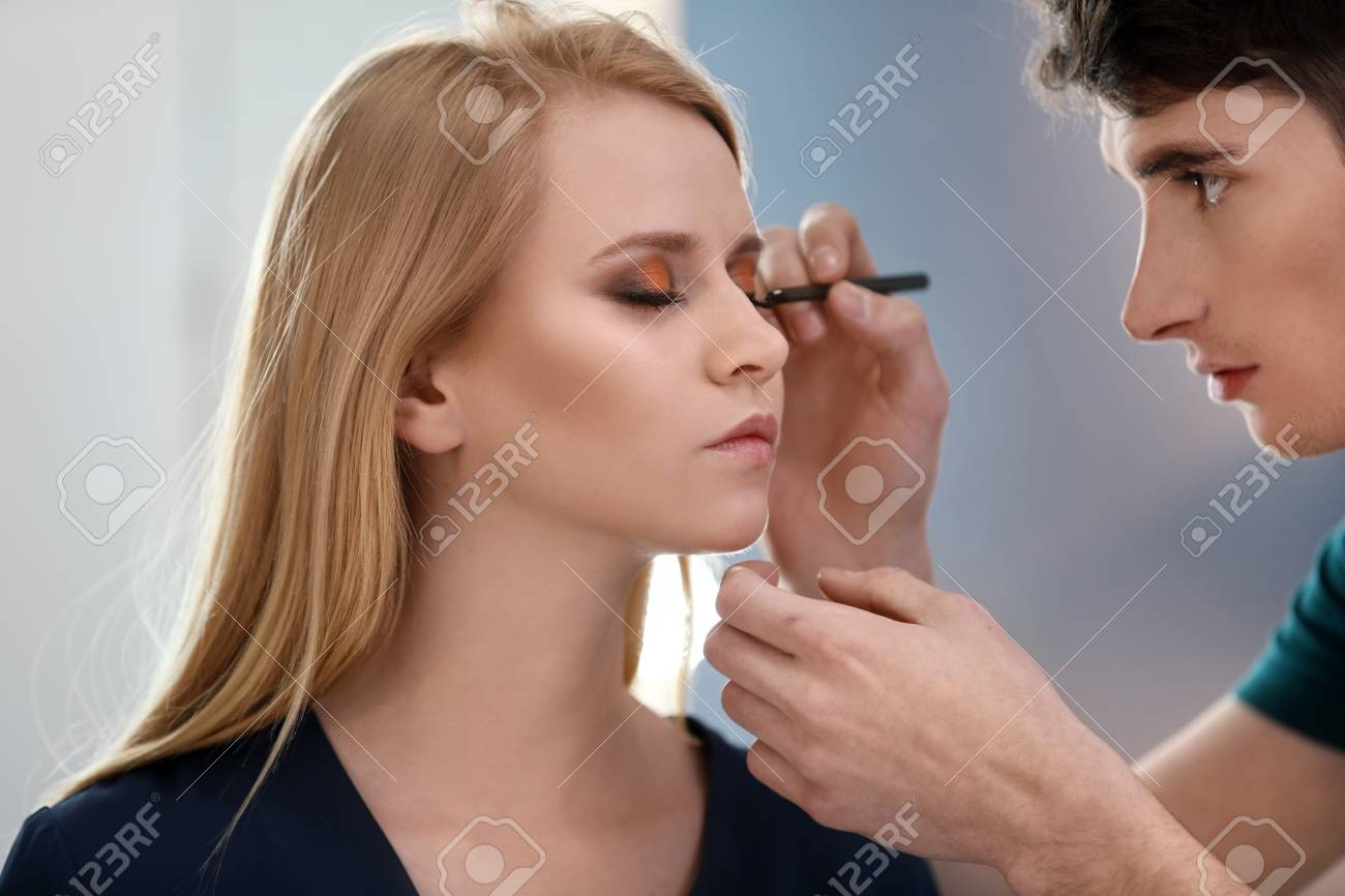 Professional Makeup Artist Working With Young Model In Salon