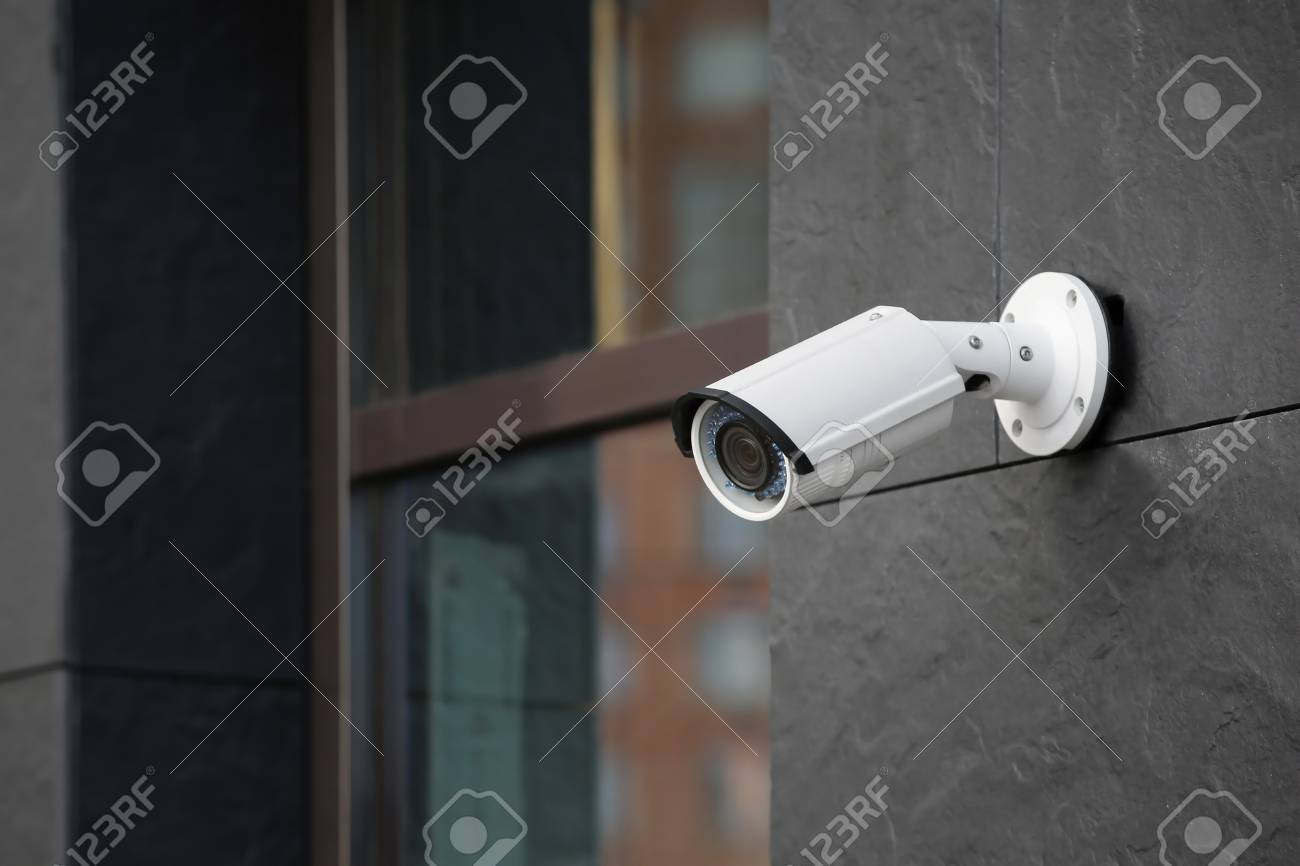 Modern CCTV camera on wall of building outdoors - 112787149