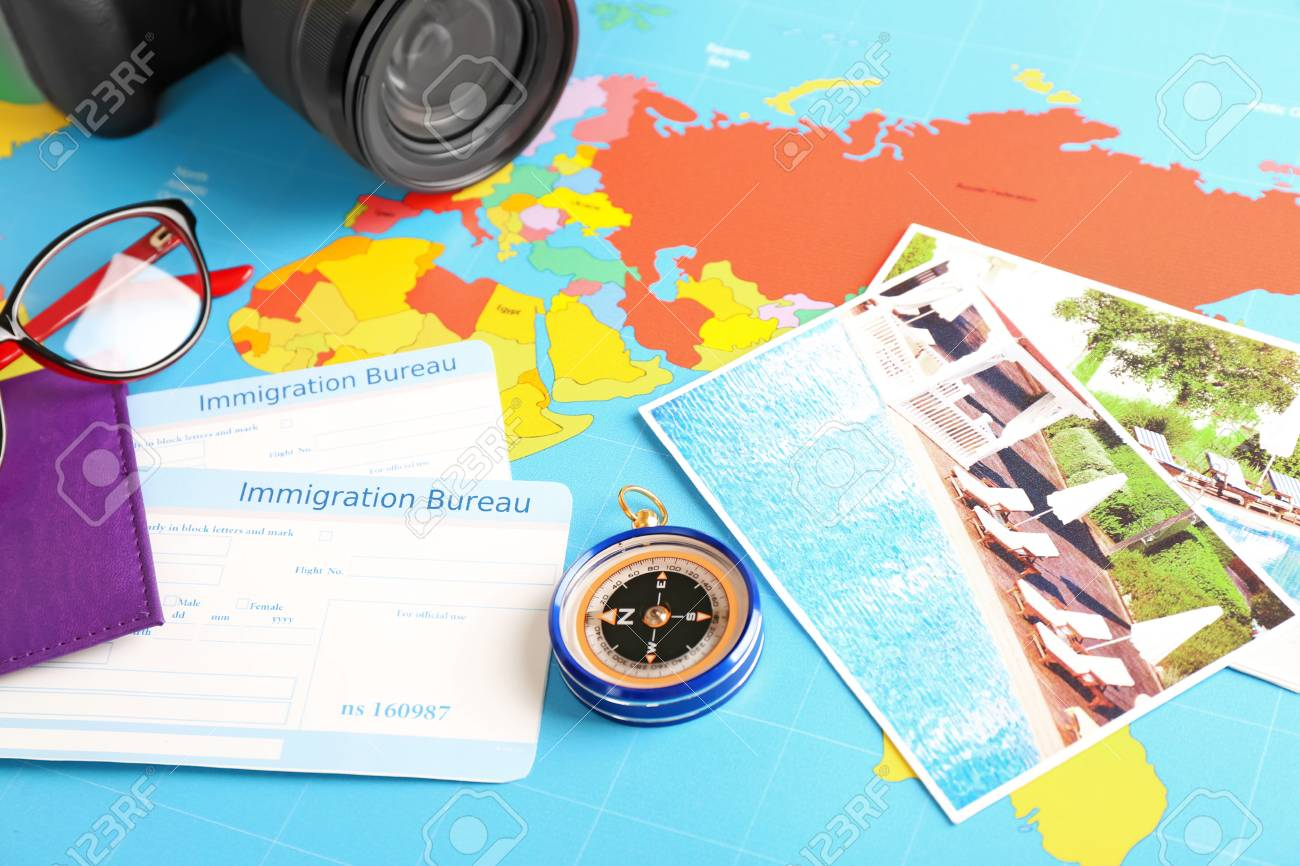 Composition with compass and immigration bureau cards on world map