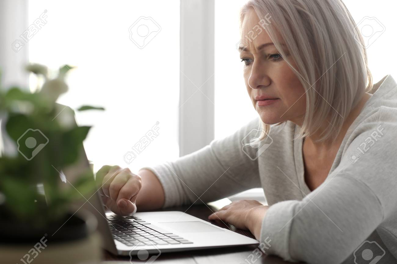 Mature woman reading news on laptop screen in cafe - 113257258