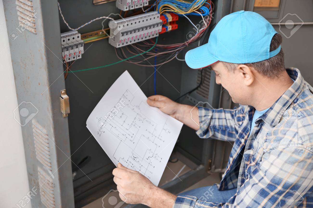 Mature electrician with circuit diagram near distribution board on electrician templates, electrician applications, electrician art, electrician statistics, electrician signs, electrician troubleshooting,