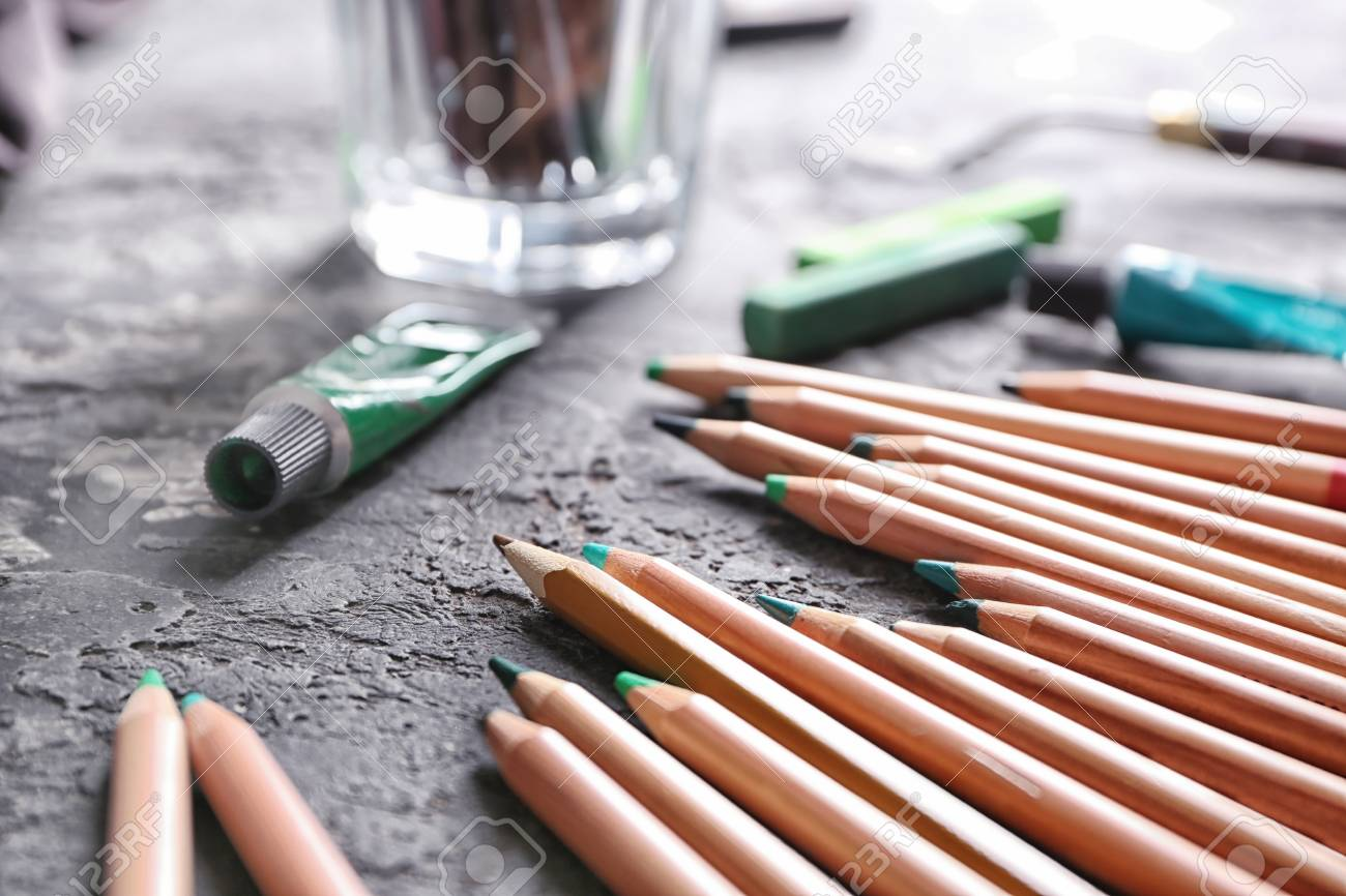 Color pencils of professional artist on table closeup
