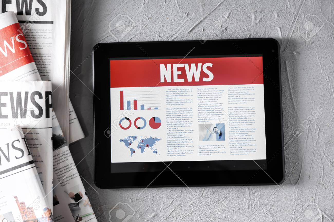 Tablet computer with news on screen on textured background - 114121923