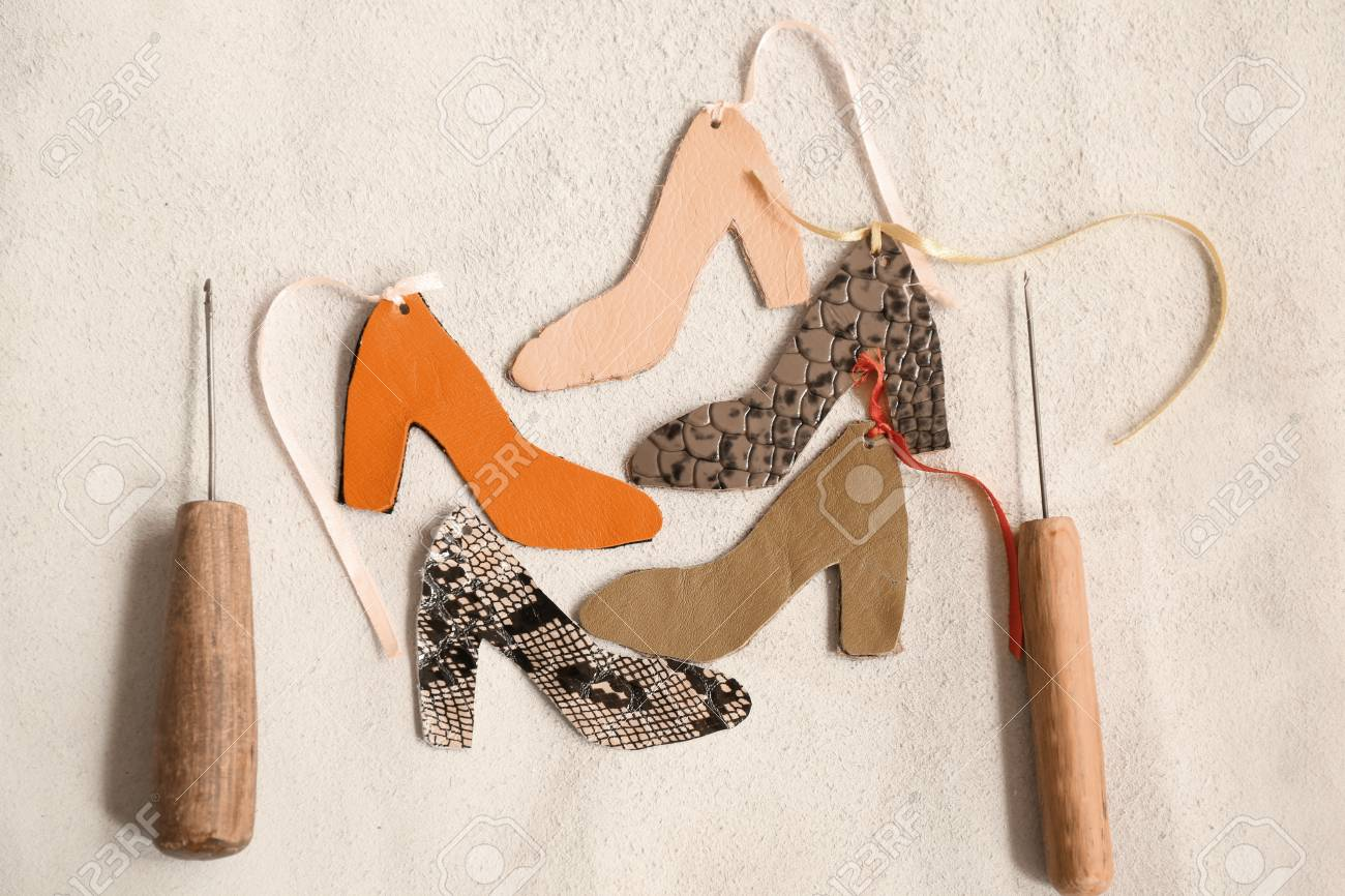 Samples Of Leather In Shape Of Shoe With Craft Tools On Light