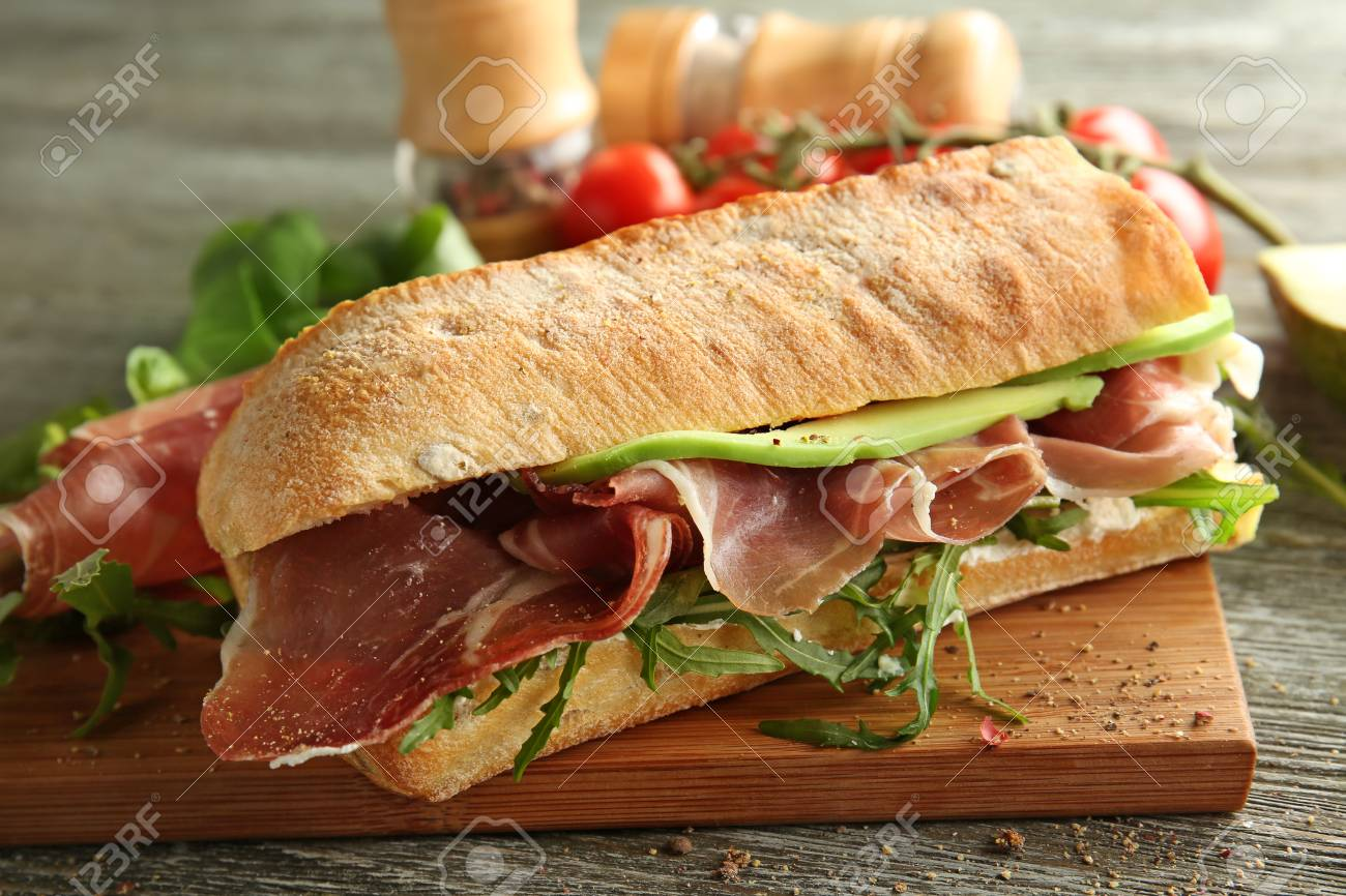 Tasty sandwich with prosciutto on wooden board, closeup - 114618355