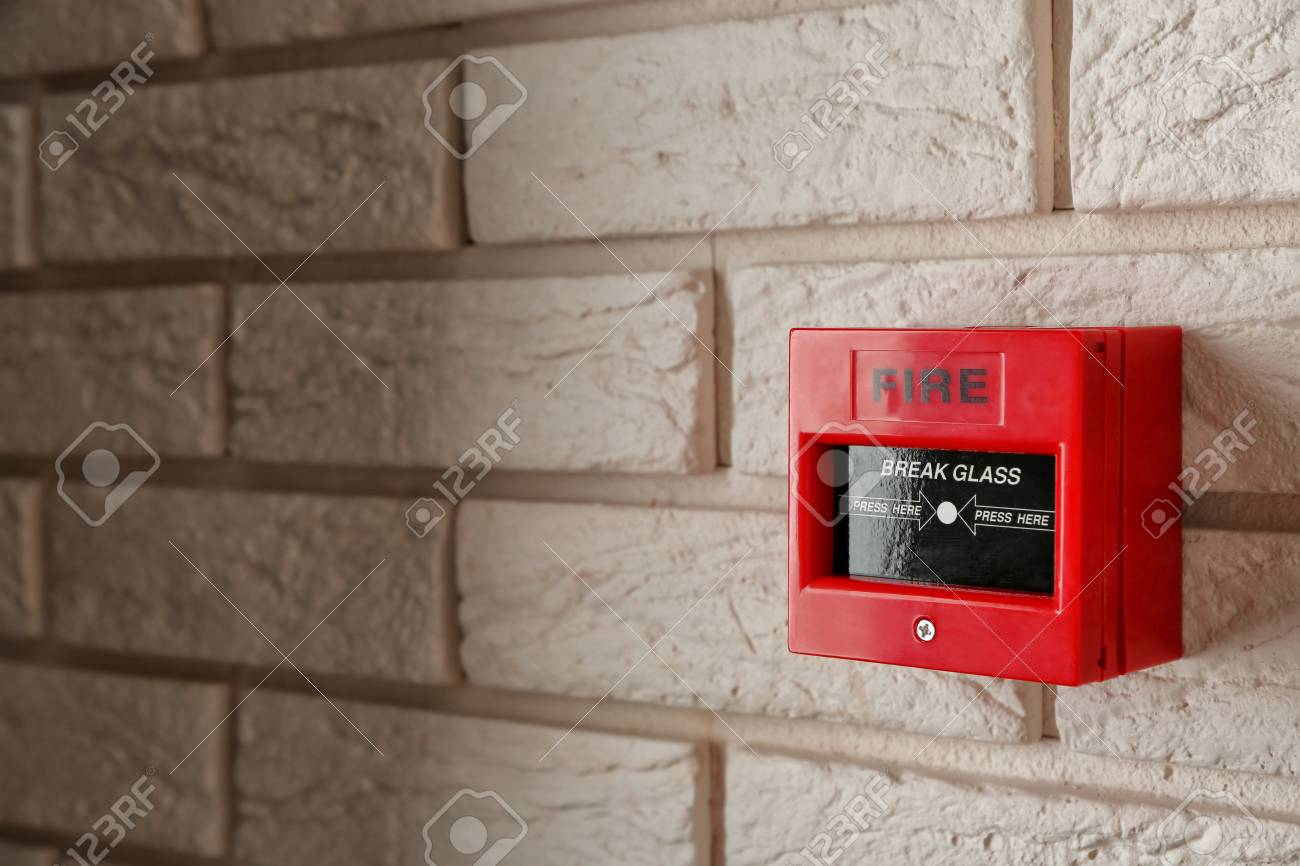 Modern fire call point on brick wall indoors - 114692111