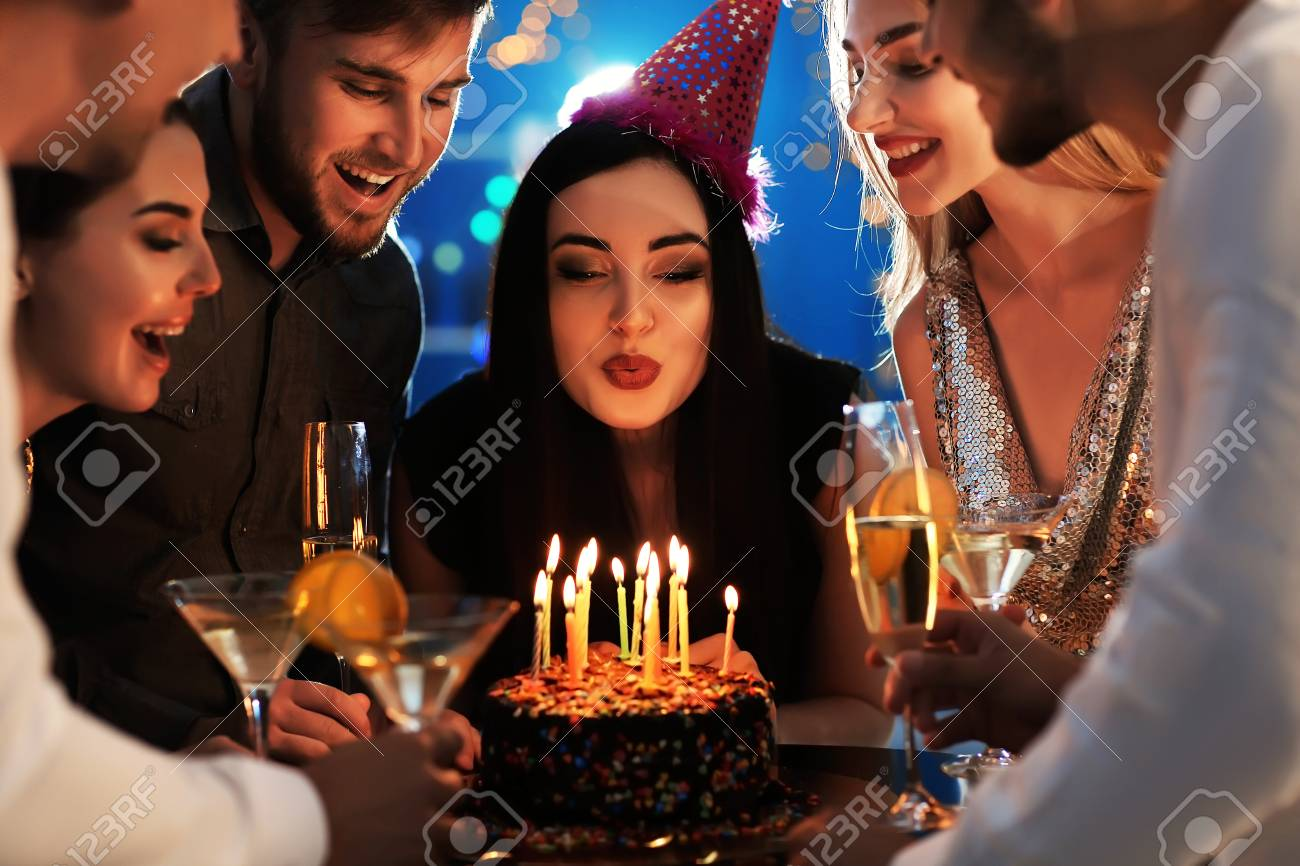Young Woman Blowing Out Candles On Her Birthday Cake With Friends