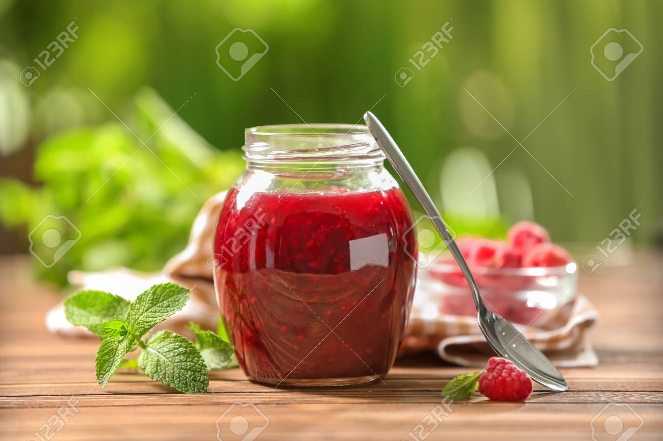 Glass jar with sweet raspberry jam on table outdoors - 114600748