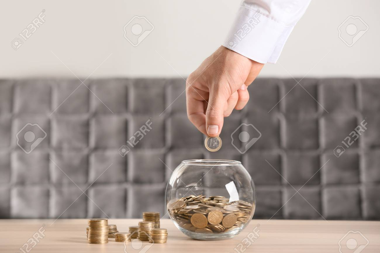 Man putting coins into glass jar on table. Savings concept - 114662646